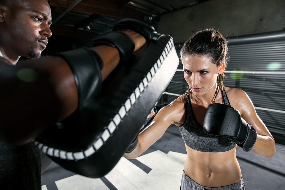 Boxing female with martial arts trainer