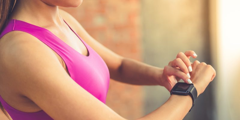 beautiful sports girl is switching on her fitbit before training
