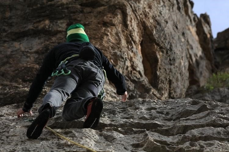 man climbing hill with climbing shoes on