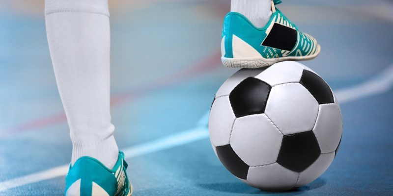Indoor football players with classic soccer ball