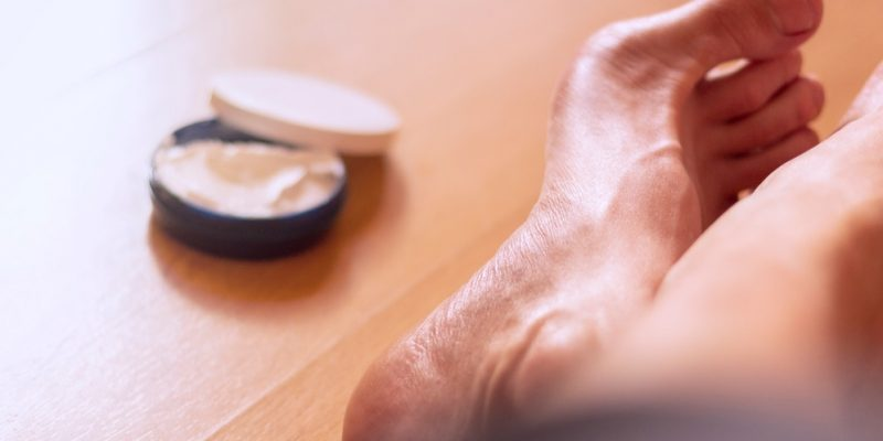 Man's bare feet on a wooden floor with a package of skin care cream next to it