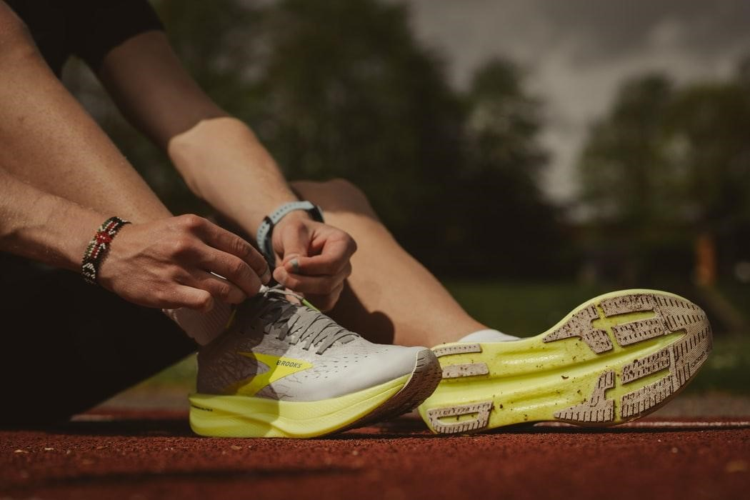 man tying running shoes on the field