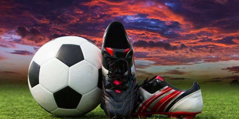 soccer ball and soccer shoes on the field of green grass