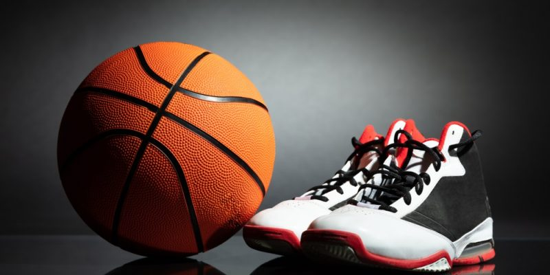 man tying sports shoes in basketball court